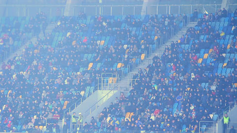 Spectators sitting on tribunes and watching football game, cold weather, fog Footage