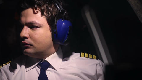 Serious professional pilot at work, checking flight indicators, talking to crew Footage