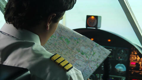 Male co-pilot checking map before operating airliner, responsibility, commitment Live Action