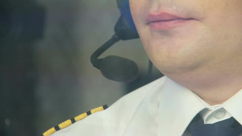 Exhausted captain operating airliner and talking to co-pilot on headset Live Action
