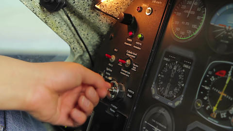 Male hand turning key to start engine, switching controls, aircraft takeoff Footage