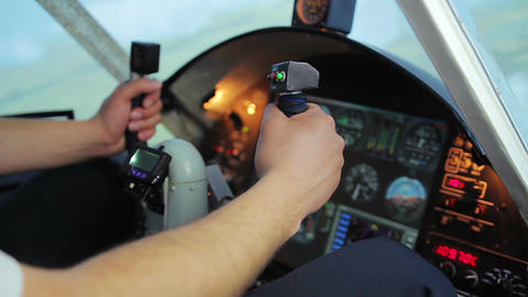 Hands of male pilot turning steering wheel, switching controls on cockpit panel Footage