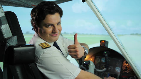 Happy pilot smiling at camera, thumbs up sign, successful career in aviation Live Action