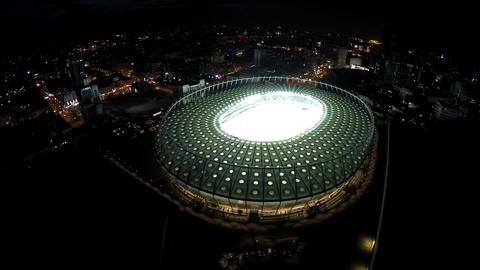 Night city sparkling with lights, aerial view of arena for sports competitions Footage
