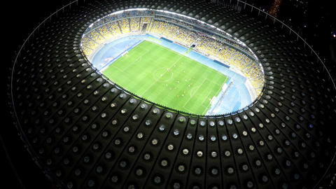 Football training on illuminated stadium, players playing soccer match at night Footage