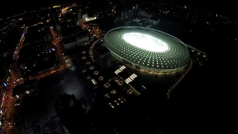Night city, aerial view on illuminated football stadium during match, sports Footage
