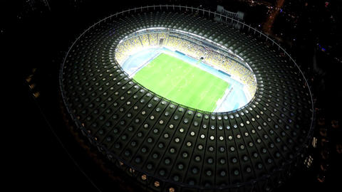 Professional players playing soccer game at large illuminated sports stadium Footage