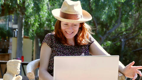 Woman sits in the garden enjoying a conversation on her laptop in the sun Footage