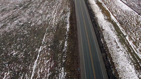 Aerial drone fly over empty lonely winter paved road that splits to 2 directions Footage