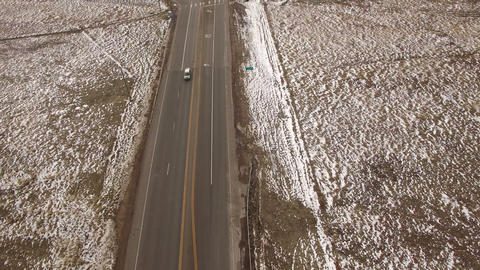 Aerial drone cars driving by winter fresh snow road landscape Footage