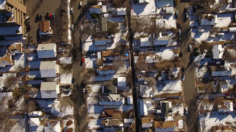 Aerial drone fly directly over snow covered winter houses to highway Footage