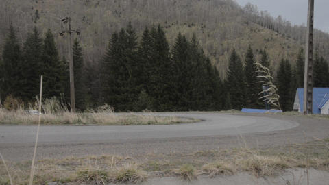 Black car rally takes a tight curve on a gloomy weather and rain bringer 1846a Footage