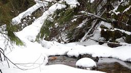 Mountain stream flowing through snow drifts 3415 Footage