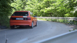 Racecars orange turns a curve at the speed 6995 Live Action