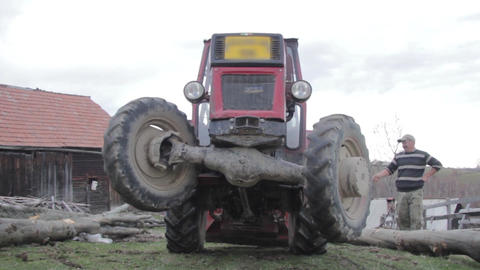 Tractor going on two wheels due to the weight that a towing after him 2072 Footage