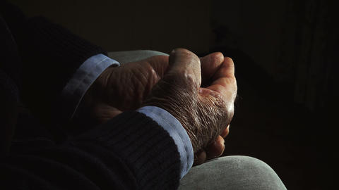hands of old retired man: elderly man sitting alone in the darkness Footage