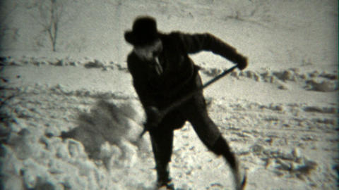 1936: Man shovels snow at camera in fedora hat and scarf wrapped head Footage