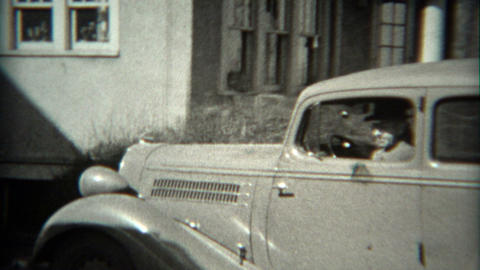 1936: Man backing car out of driveway in Ford 1934 model vehicle Footage