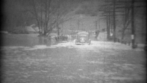 1936: Townspeople helping car get across water flooded road Footage