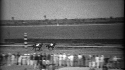 1935: Horses coming around the corner in race at old time racetrack Footage