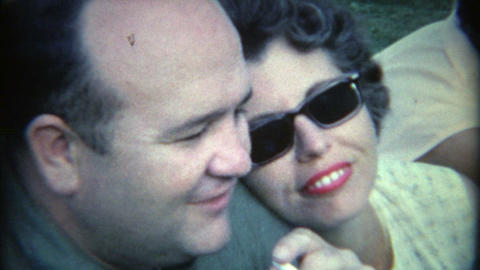 1965: Man smoking cigarette with wife lovingly watching him Footage