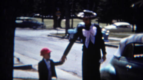 1957: Woman exits car giant pink bow scarf matching hat for holiday festive wave Footage