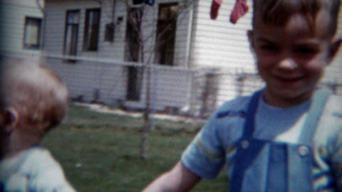 1957: Baby brothers playing modest backyard together matching blue overalls Footage