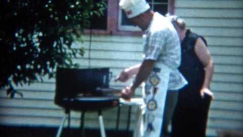 1957: Mother in black giving cook son hard time grilling outdoor chef hat Footage