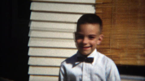 1957: Kid dressed up formal black tie white shirt tuxedo top pleasantry Footage