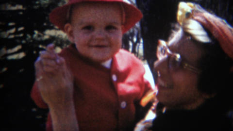 1957: Proud nerdy mom holds big baby boy red gangster style suit Footage