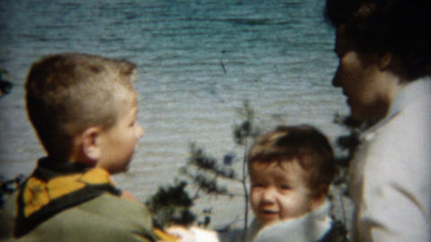 1955: Mother giving boy scout advice with young baby girl present Footage