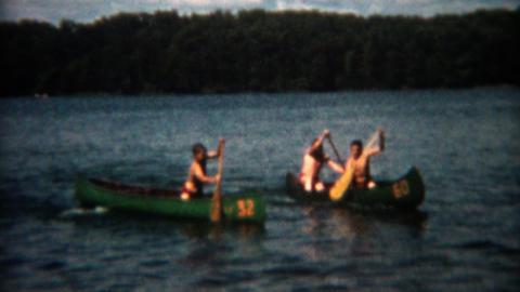 1955: Canoe racing across the lake at summer camp rental watercraft Footage