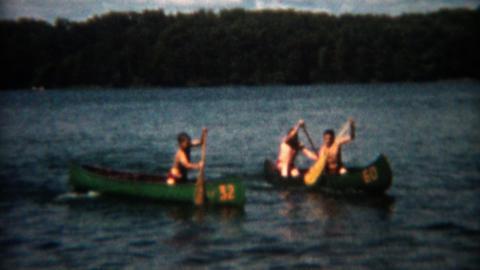 1955: Canoe racing across the lake at summer camp rental watercraft Footage