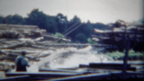 1949: Timber logs splashing water process man stick overalls for safety Footage
