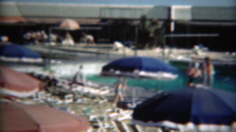 1949: Poolside pan of loungers enjoying summer sun colorful umbrellas Footage