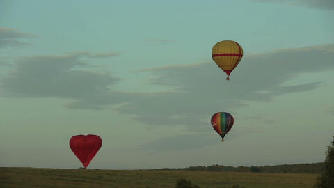 hot air balloons flying over field in countryside Footage