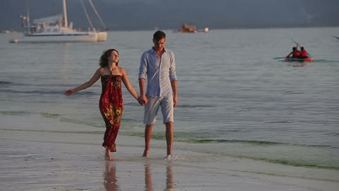 Couple walk together along the beach at sunset Footage