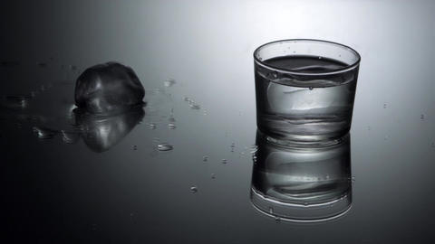 Pouring water into glass with ice cubes Footage