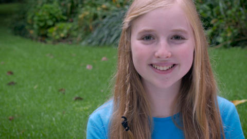 An adorable young blond haired girl smiles and looks at the camera while sitting Footage
