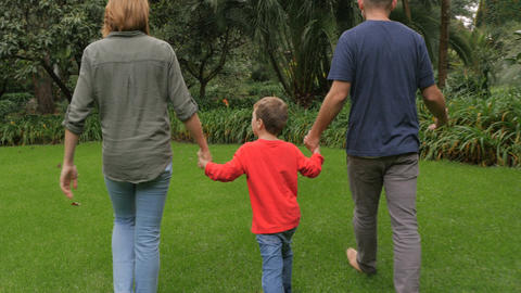 Steadicam of a father and mother holding hands with their son shot from behind a Footage