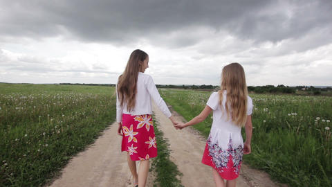 Young girls walking holding their hands Footage