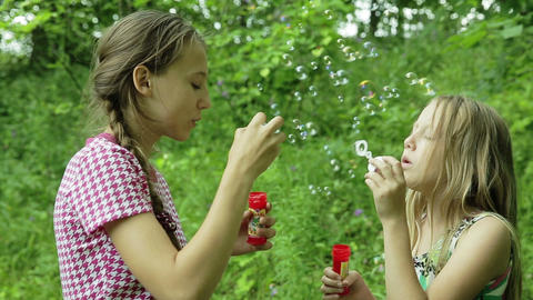 Young girls blowing soap bubbles outdoor Footage