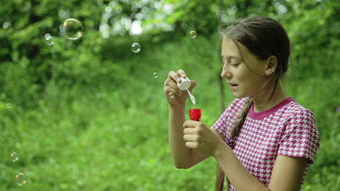 Young girl blowing soap bubbles outdoor Footage