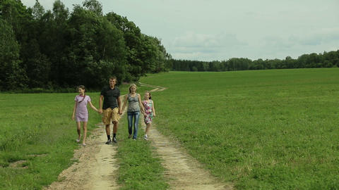 Happy family walking country road holding hands Footage