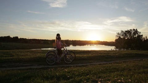 Young girls go with bikes,sunset, ake,silhouettes Footage