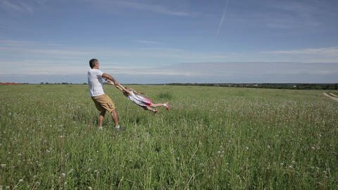 Father playing with his daughter in field Footage