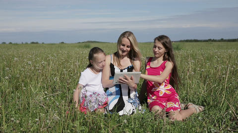 Woman and daughter using tablet computer in field Footage