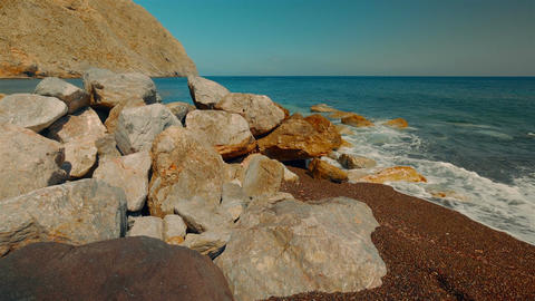 Tilting Shot Of A Mediterranean Volcanic Beach With Red Sand And Surf Hitting Th stock footage