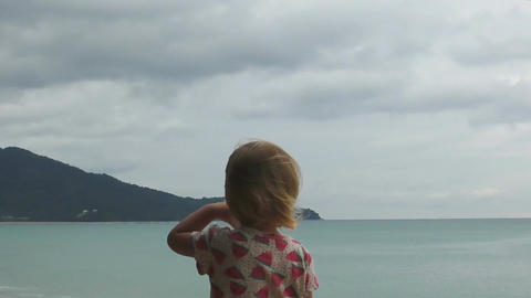 Little blonde girl straightens her hair in the wind Footage