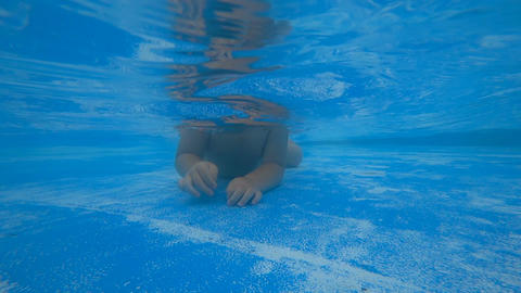 Little child crawling on the bottom of swimming pool Footage